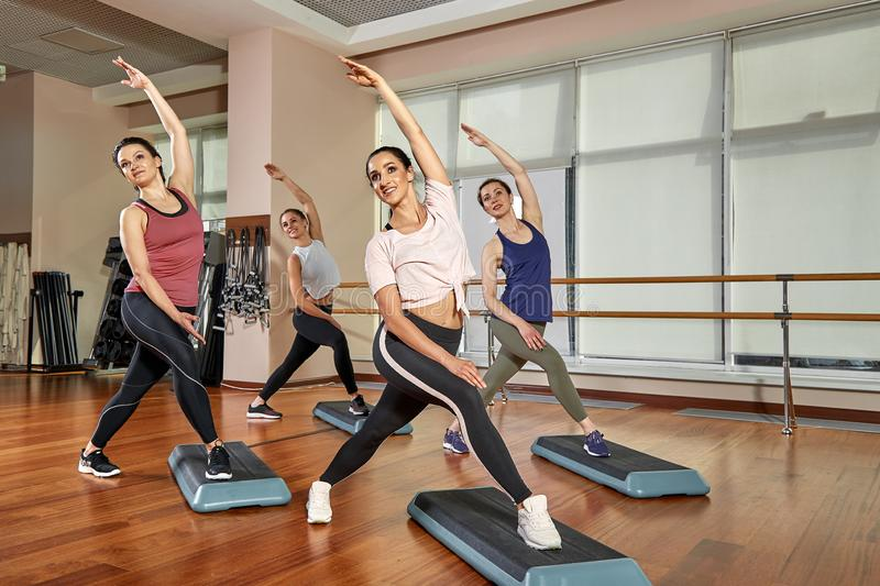 Group of young sporty attractive people practicing yoga lesson with instructor, standing together in exercise, working. Out, full length, studio background stock photos