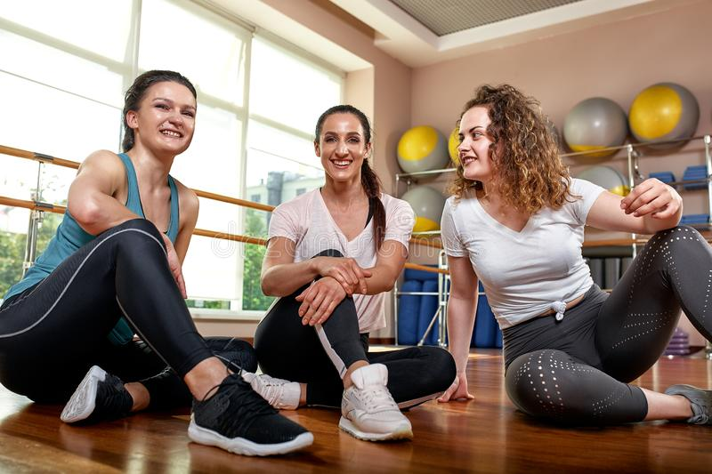 Group of young sporty attractive people practicing yoga lesson with instructor, standing together in exercise, working. Out, full length, studio background royalty free stock images