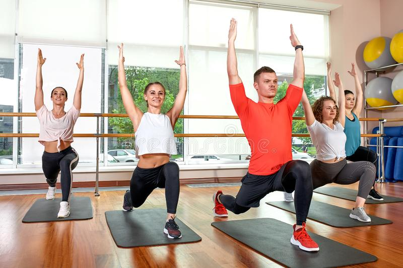 Group of young sporty attractive people practicing yoga lesson with instructor, standing together in exercise, working. Out, full length, studio background royalty free stock photos