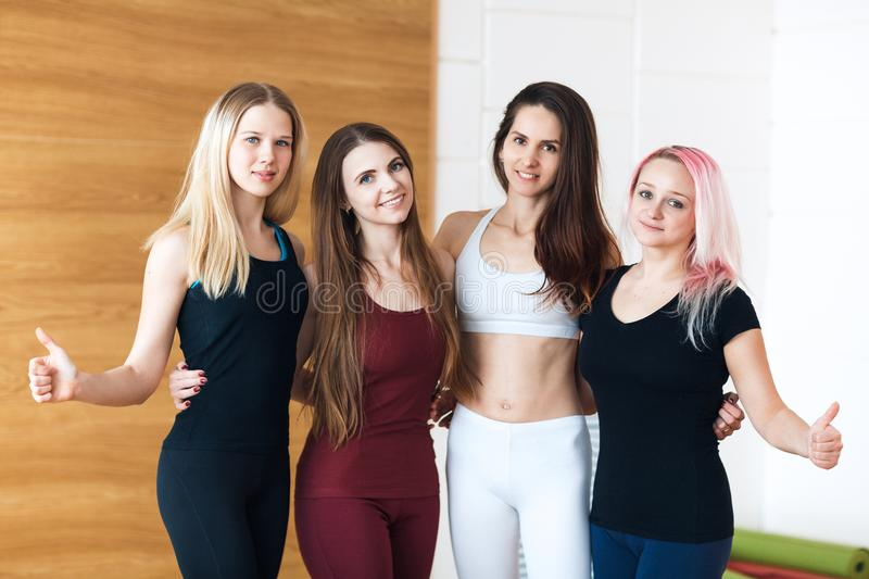 Group of young sporty girls showing thumbs up while standing at white interior of loft studio. Female companions in gym resting af royalty free stock photography