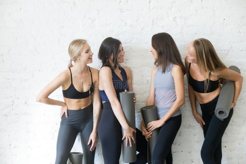 Group of young sporty girls with yoga mats talking royalty free stock photos