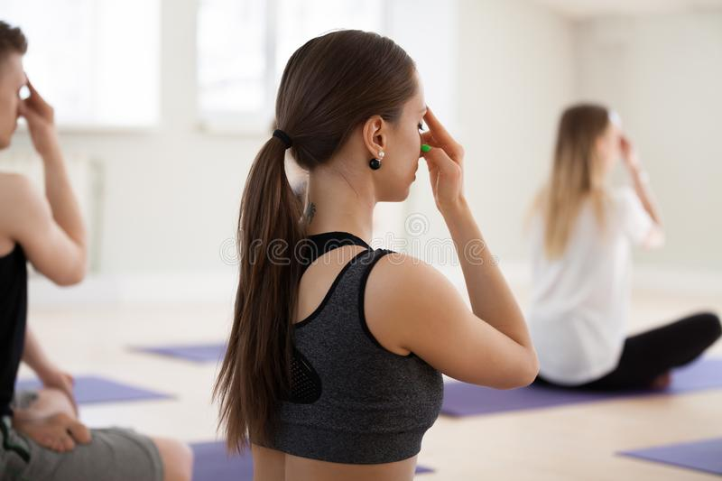 Group of young sporty people doing Alternate Nostril Breathing e. Group of young sporty people doing yoga, Alternate Nostril Breathing exercise, nadi shodhana stock photo
