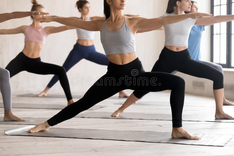 Group of young people practicing yoga lesson doing Warrior II royalty free stock photo