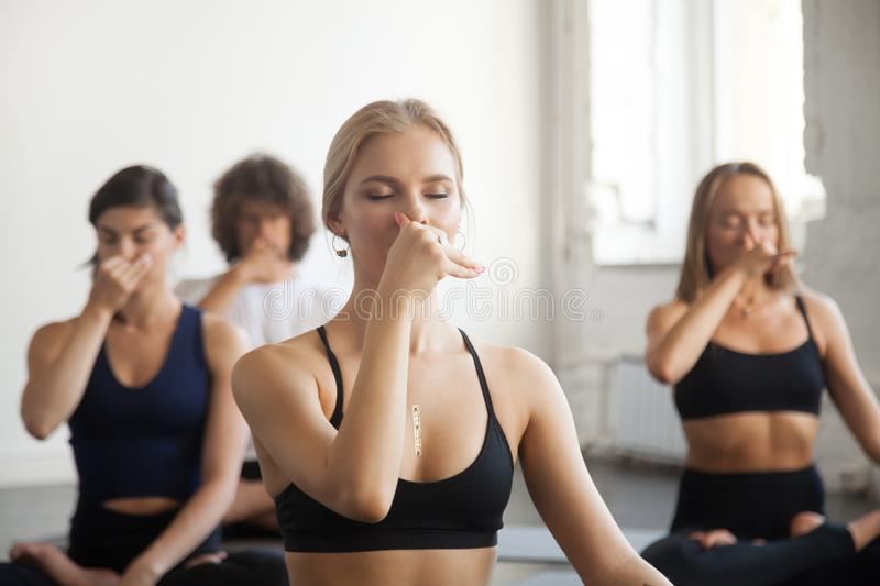 Group of young sporty people making Alternate Nostril Breathing. Group of young sporty people practicing yoga lesson with instructor, making Alternate Nostril royalty free stock photos