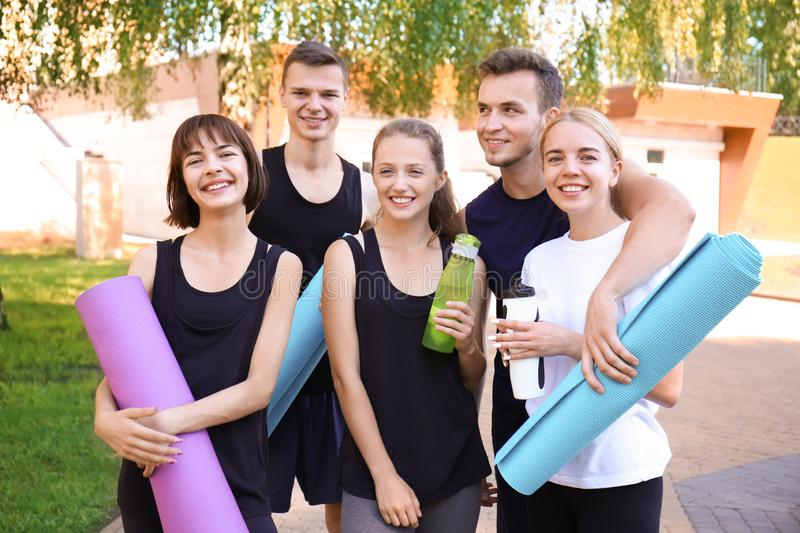 Group of young sporty people with mats outdoors stock photography