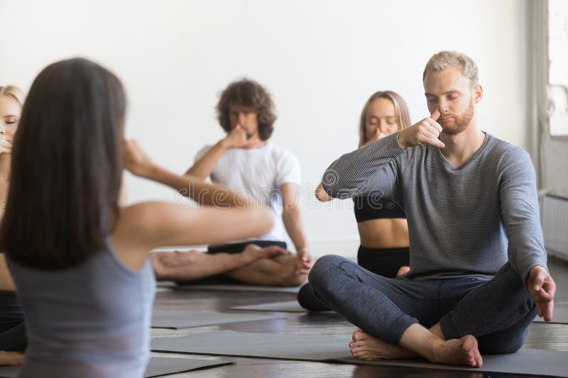 Group of young sporty people making Alternate Nostril Breathing. Group of young sporty people practicing yoga lesson with instructor, sitting, making Alternate stock photos