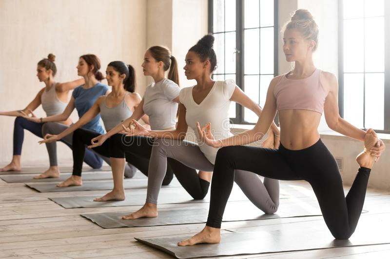 Group of young sporty women practicing yoga, doing Horse rider royalty free stock images