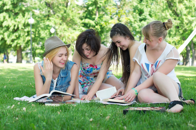 Group of young student using laptop together. In the park stock images