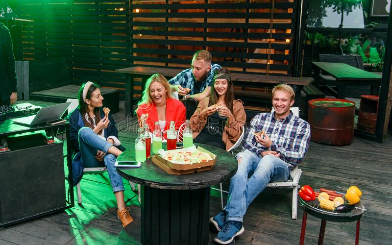 Group of young people sitting around and eating pizza. Friends partying and eating pizza. stock images