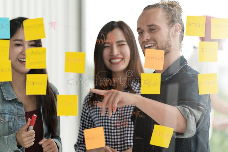 Group of young successful creative multiethnic team smile and brainstorm on project together in modern office with post note or st stock photo