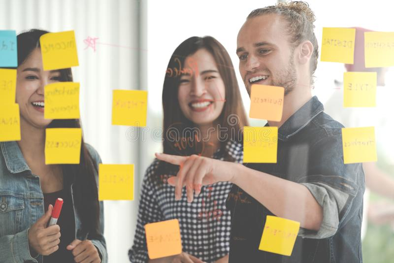 Group of young successful creative multiethnic team smile and brainstorm on project together in modern office with post note or st. Icky note. Caucasian men royalty free stock photo