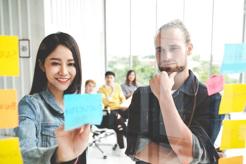 Group of young successful creative multiethnic team smile and brainstorm on project together in modern office. Woman sticking. And look at sticky note on glass stock photography