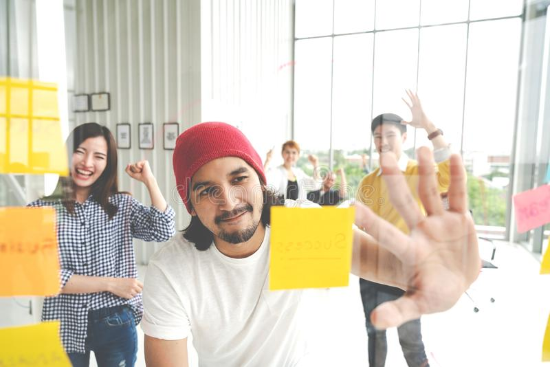 Group of young successful creative multiethnic team smiling and brainstorm together in meeting. Happy hispster asian man looking. At sticky post note on glass royalty free stock photo