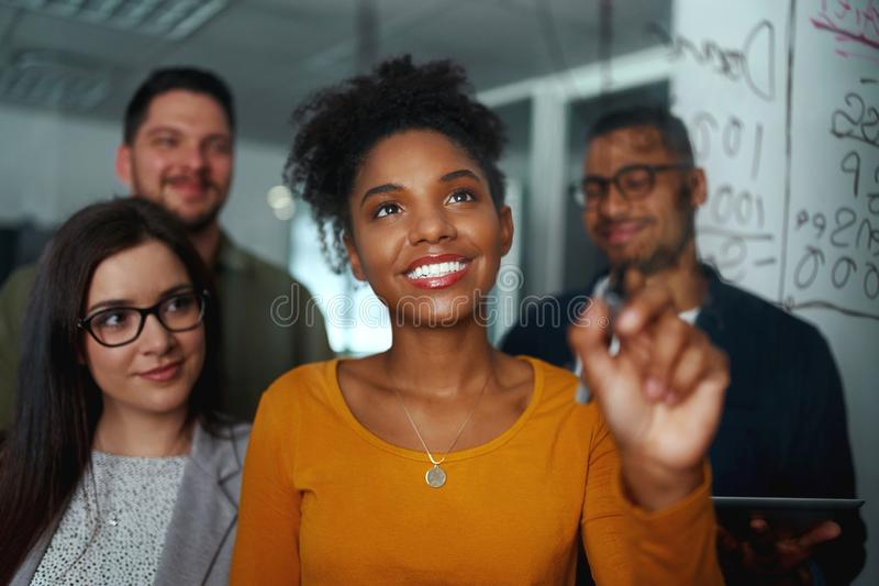 Group of young successful creative multiethnic team smiling and working together in modern office royalty free stock photos