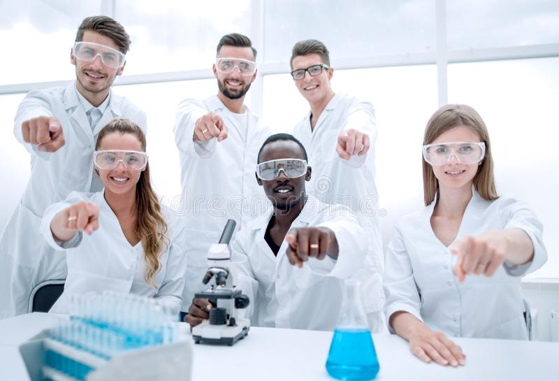 Group of young successful scientists posing for camera stock photos