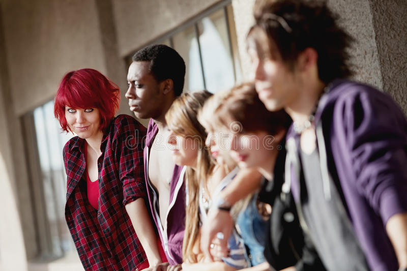 Group of young teens staring into distance. A group of young punk rock teens stare off into the distance as one looks towards the camera stock photo