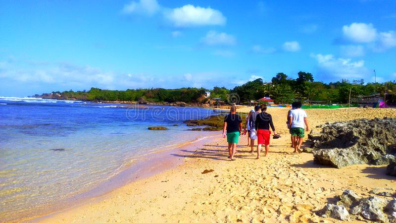 Group of young teens walking along the beach. Location: Pangasinan, Philippines. Nature, seacape, ocean, pure, white, sand, rock, clear, water, buesky stock photo