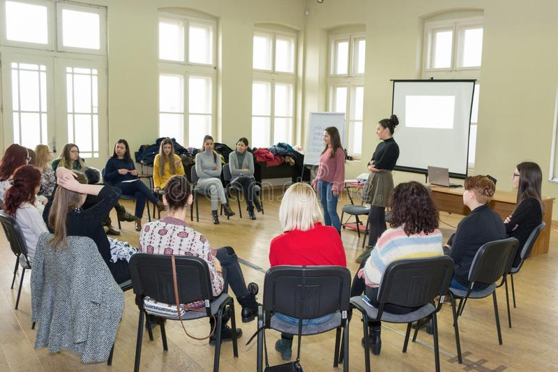 Group of young university students having a group discussion sitting together on a circle of chairs and talking stock photo