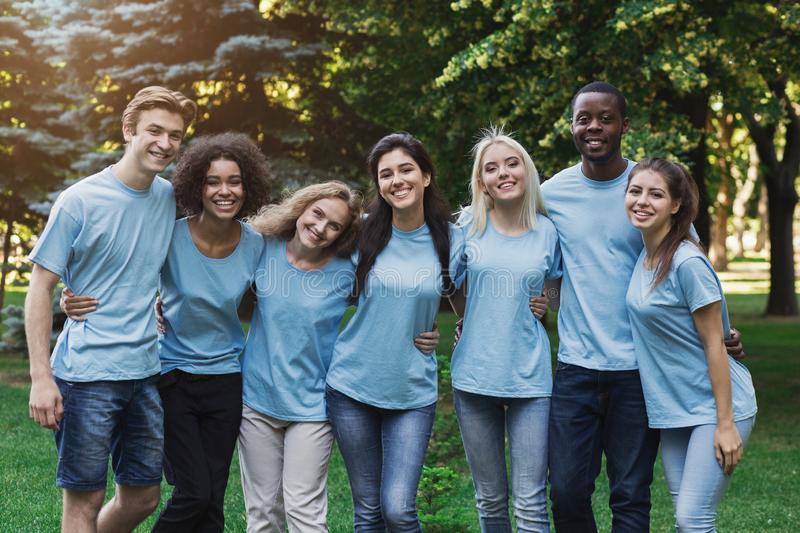 Group of young volunteers embracing at park stock photos
