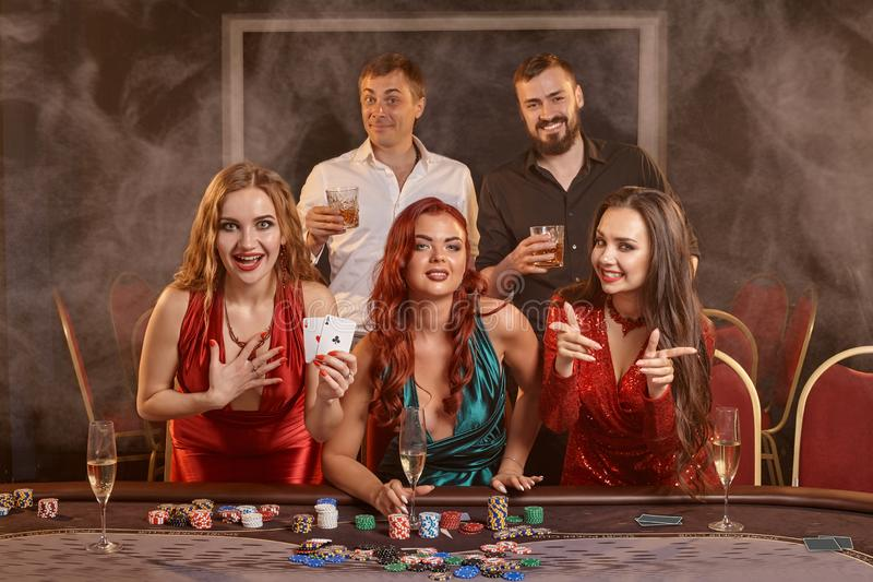 Group of a young wealthy friends are playing poker at a casino. royalty free stock photography