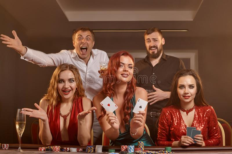 Group of a young wealthy friends are playing poker at a casino. royalty free stock image