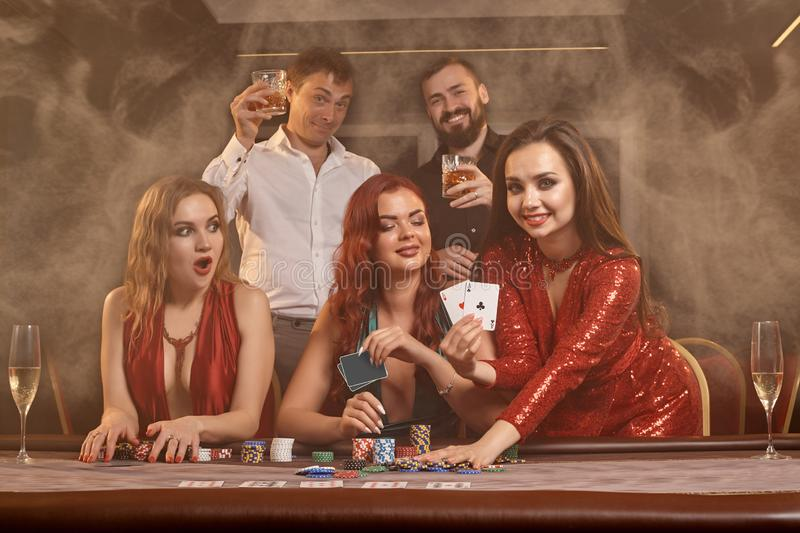 Group of a young wealthy friends are playing poker at a casino. royalty free stock photo