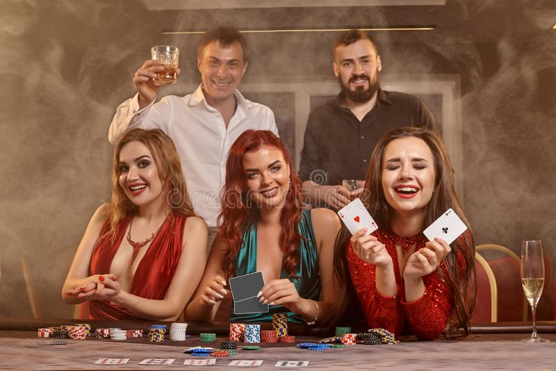 Group of a young wealthy friends are playing poker at a casino. stock image