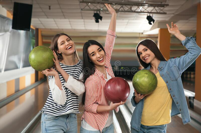 Group of young women with balls in bowling royalty free stock images