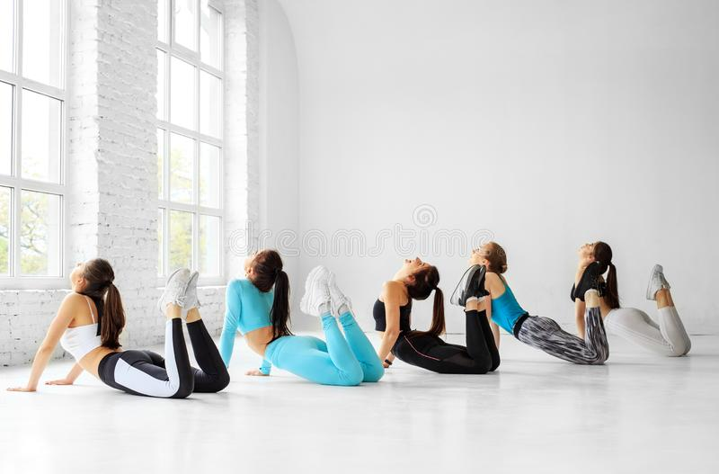 A group of young women is engaged in stretching in the gym. The concept of sports, healthy lifestyle, fitness, stretching royalty free stock photography