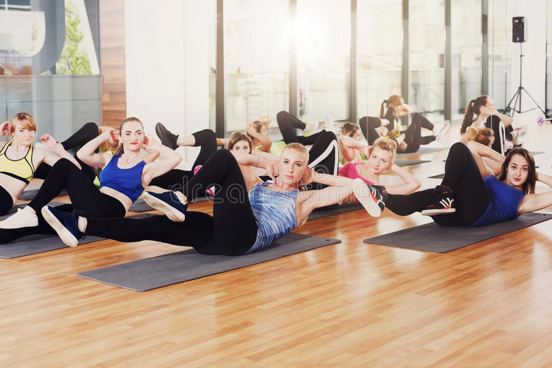 Group of young women in the fitness class, cross crunches stock image