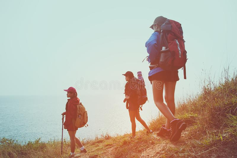 Group young women of hikers walking with backpack on a mountain at sunset. Traveler going camping. Travel Concept stock photo