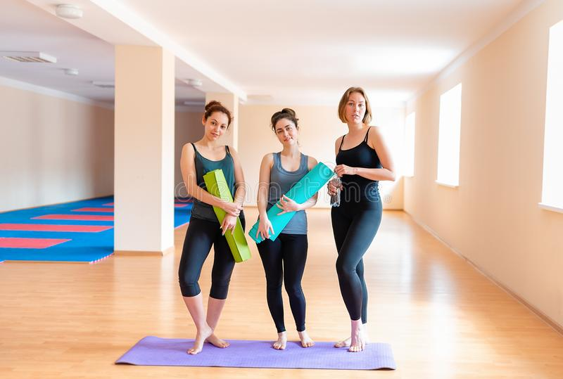 A group of young women with mats in their hands posing for the camera. The concept of sports lifestyle, gymnastics and yoga royalty free stock photos