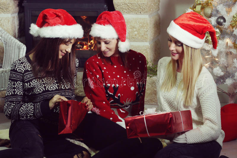 Group young women sitting at the fireplace. At Christmas stock image