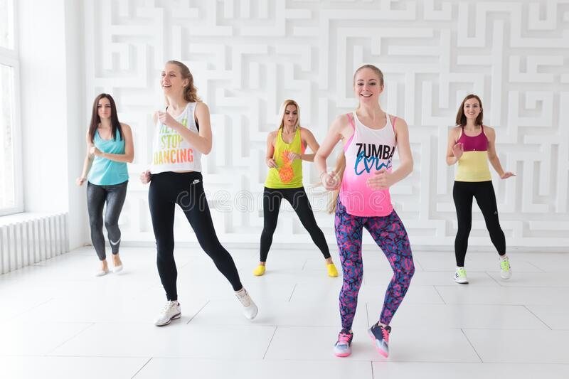 Group of young women in sportswear at dance class in white studio. Group of young women in sportswear at Zumba dance class in white studio stock image