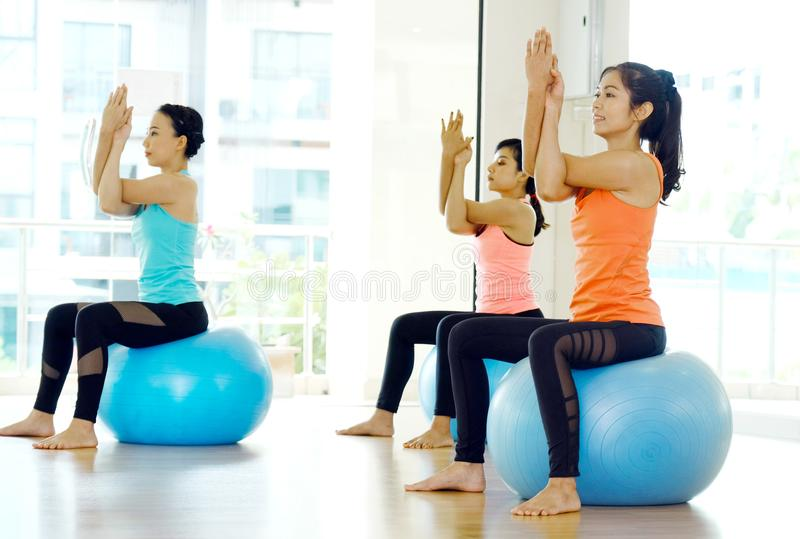 Group of young women stretching body on yoga balls in studio practice class, wellness, well being, healthy lifestyle stock image