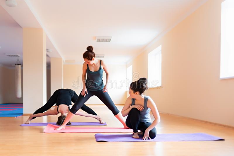 A group of young women warm up before training in the gym. The concept of sports lifestyle, gymnastics and yoga stock photos