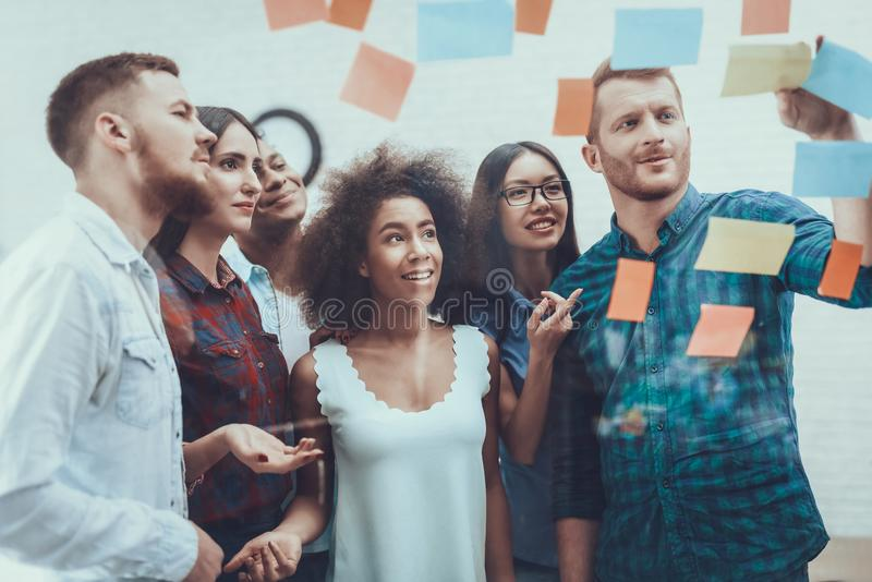 Group of Young Workers . Glass with Stickers. royalty free stock image