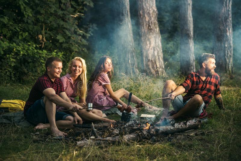 Group of youngsters camping in woods. Two couples frying sausages over campfire. Excited guy calling, welcoming friends royalty free stock photo