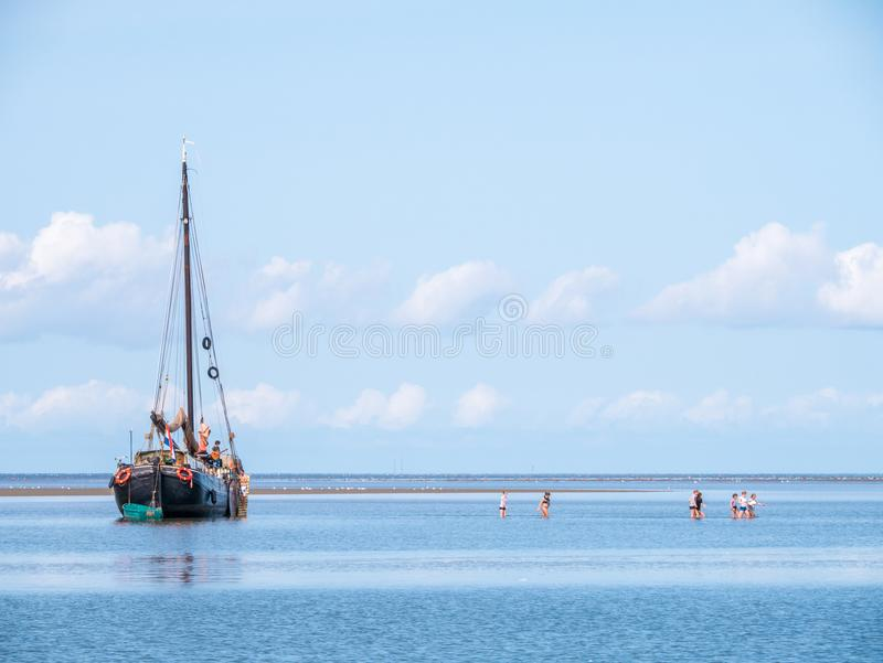 Group of youngsters wading in shallow water and sailboat aground stock image