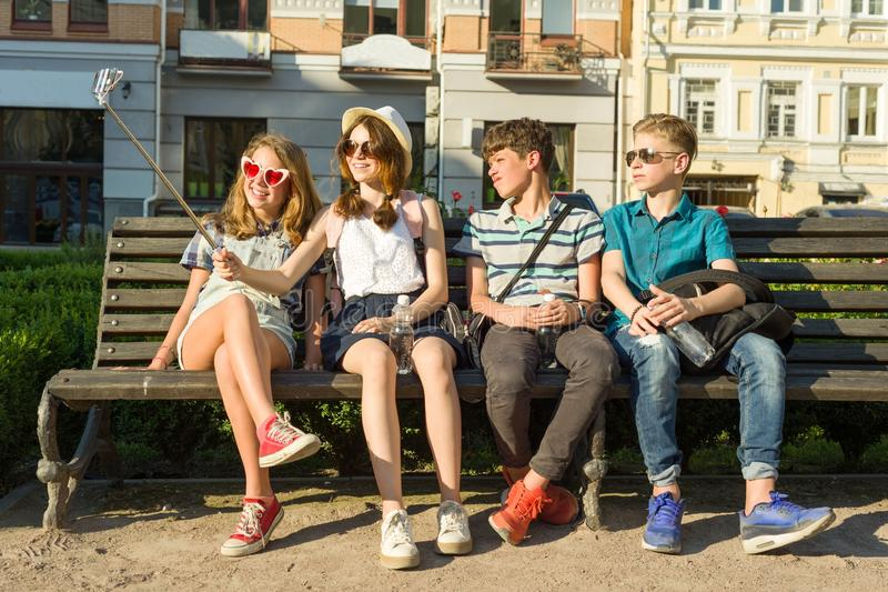 Group of youth is having fun together outdoors in urban background. Summer holidays, education, teenage concept. royalty free stock image
