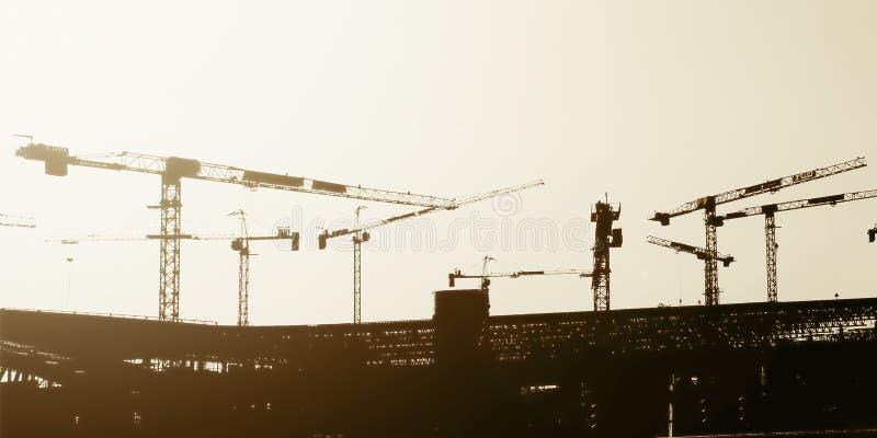 Groupe artistique de silhouette de vue de panorama de grues à tour travaillant au chantier de construction photographie stock libre de droits