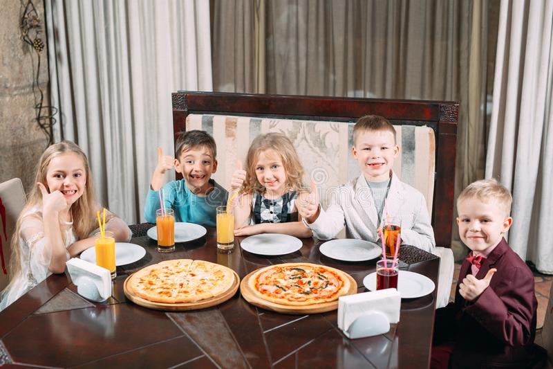 Groupe of Children eat pizza in the restaurant. stock photos