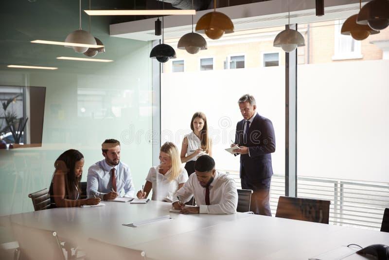 Groupe collaborant sur la tâche au jour licencié d'évaluation de recrutement tandis qu'étant observé par l'équipe de recrutement photos libres de droits