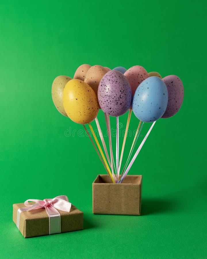 Groupe coloré de ballons d'oeuf de pâques avec le boîte-cadeau sur le fond vert concept créatif minimal image libre de droits