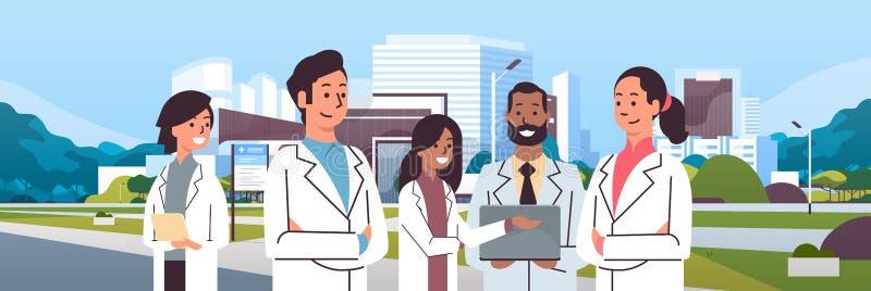 Groupe d'équipe de médecins de course de mélange dans l'uniforme se tenant ensemble au-dessus de l'extérieur moderne de clinique  illustration de vecteur