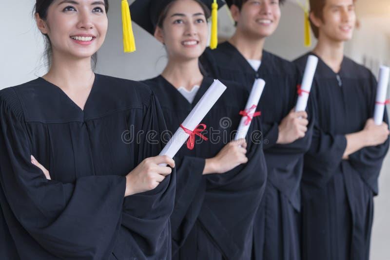 Groupe d'étudiant réussi leur jour, diplôme se tenant licencié, éducation, obtention du diplôme et concept de personnes photos stock