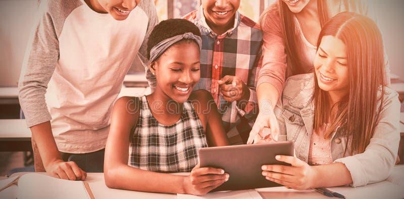 Groupe d'étudiants à l'aide du comprimé numérique dans la salle de classe photo stock