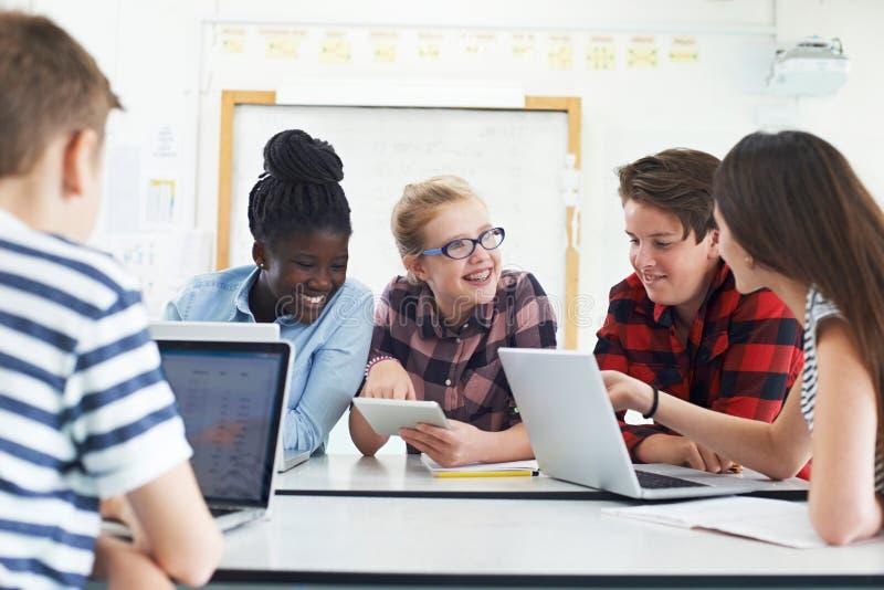 Groupe d'étudiants adolescents collaborant sur le projet dans la classe informatique photographie stock libre de droits