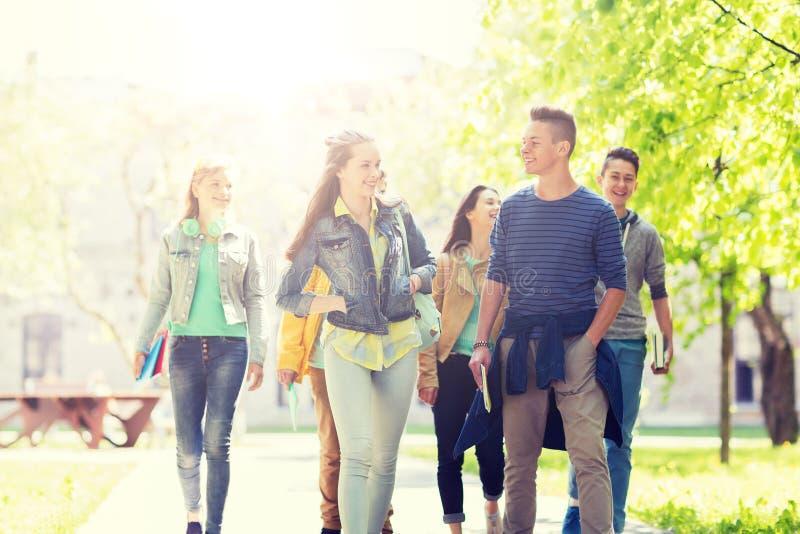 Groupe d'étudiants adolescents heureux marchant dehors photo libre de droits