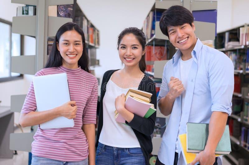 Groupe d'étudiants asiatique tenant les livres et l'ordinateur portable dans la bibliothèque, learni image libre de droits